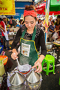 17 OCTOBER 2012 - BANGKOK, THAILAND:  A desert vendor works on vegan Thai snacks at the Vegetarian Festival food fair on Yaowarat Road in Chinatown in Bangkok. The Vegetarian Festival is celebrated throughout Thailand. It is the Thai version of the The Nine Emperor Gods Festival, a nine-day Taoist celebration celebrated in the 9th lunar month of the Chinese calendar. For nine days, those who are participating in the festival dress all in white and abstain from eating meat, poultry, seafood, and dairy products. Vendors and proprietors of restaurants indicate that vegetarian food is for sale at their establishments by putting a yellow flag out with Thai characters for meatless written on it in red.       PHOTO BY JACK KURTZ