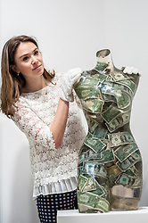 """© Licensed to London News Pictures. 08/06/2015. London, UK. A Sotheby's staff member looks at """"Venus aux dollars"""" by Arman (est. £16,000 - £22,000), at the preview of """"To the Bearer on Demand"""", a private collection of 21 works inspired by the US dollar, including Andy Warhol masterpieces, which will be auctioned on 1 and 2 July.  The collection is estimated to realise £50 million. Photo credit : Stephen Chung/LNP"""