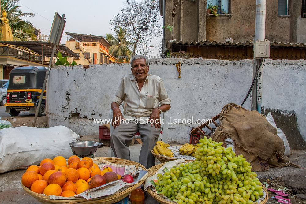 India, Uttar Pradesh, Varanasi, happy smiling mature street vendor selling fruit in the market