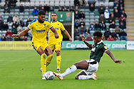 Jake Jervis (10) of AFC Wimbledon is tackled by Ashley Smith-Brown (23) of Plymouth Argyle during the EFL Sky Bet League 1 match between Plymouth Argyle and AFC Wimbledon at Home Park, Plymouth, England on 6 October 2018.