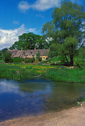 Cottages in Upper Slaughter, Gloucestershire. In the foreground is the River Eye, United Kingdom