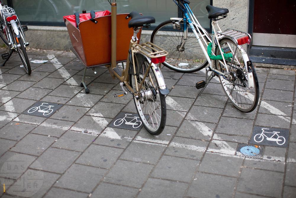 Bij een Albert Heijn in Amsterdam staan fietsen in de aangegeven parkeervakken.<br /> <br /> Bicycles are parked in a parking slot near a supermarket in Amsterdam.