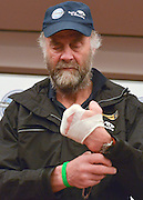 """© Licensed to London News Pictures. 04/03/2013. Heathrow, UK SIR RANULPH FIENNES looks at his bandaged left hand. . Explorer Sir Ranulph Fiennes returns to the UK after pulling out of """"The Coldest Journey"""" Expedition to the Antarctic at winter due to frostbite. The Coldest Journey Press Conference today 4th March 2013 at Heathrow Airport. Photo credit : Stephen Simpson/LNP"""