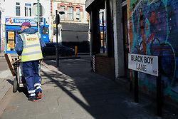 © Licensed to London News Pictures. 22/10/2021. London, UK. A council worker walks past Black Boy Lane street sign in north London. Sadiq Khan, Mayor of London has unveiled £25,000 grants to help local communities to change street names as part of a diversity campaign launched following the Black Lives Matter protests. Haringey Council in north London has already moved to change the Black Boy Lane street name. Photo credit: Dinendra Haria/LNP