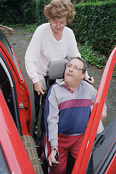 Carer helping man with Cerebral Palsy get into car,