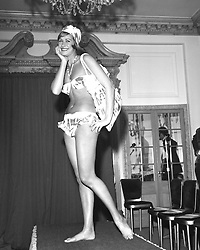 Aldine Honey models a bikini, mob cap and shoulder bag by Saville Sportswear in a 1961 spring-summer fashion display in London.