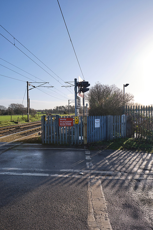 Looking towards Ipswich on the Great Eastern Main Line in Baylham. Level crossing telephone & warning sign to not trespass.<br /> Photo by Jonathan J Fussell, COPYRIGHT 2020