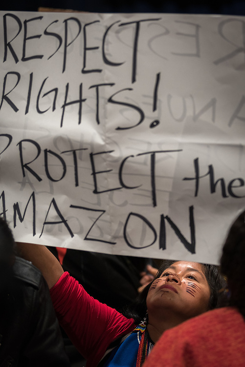 """11 December 2019, Madrid, Spain: In indigenous woman holds a sign reading """"Respect, Rights, Protect the Amazon,"""" as hundreds of civil society and other actors hold an unauthorized protest outside the plenary hall of COP25 in Madrid, to draw attention to the failures of the climate talks and to call on rich countries to step up and pay up for real solutions, and to highlight the threat of loopholes, false solutions like carbon markets, and the need for those who caused the climate crisis to pay up for loss and damage while respecting human rights."""