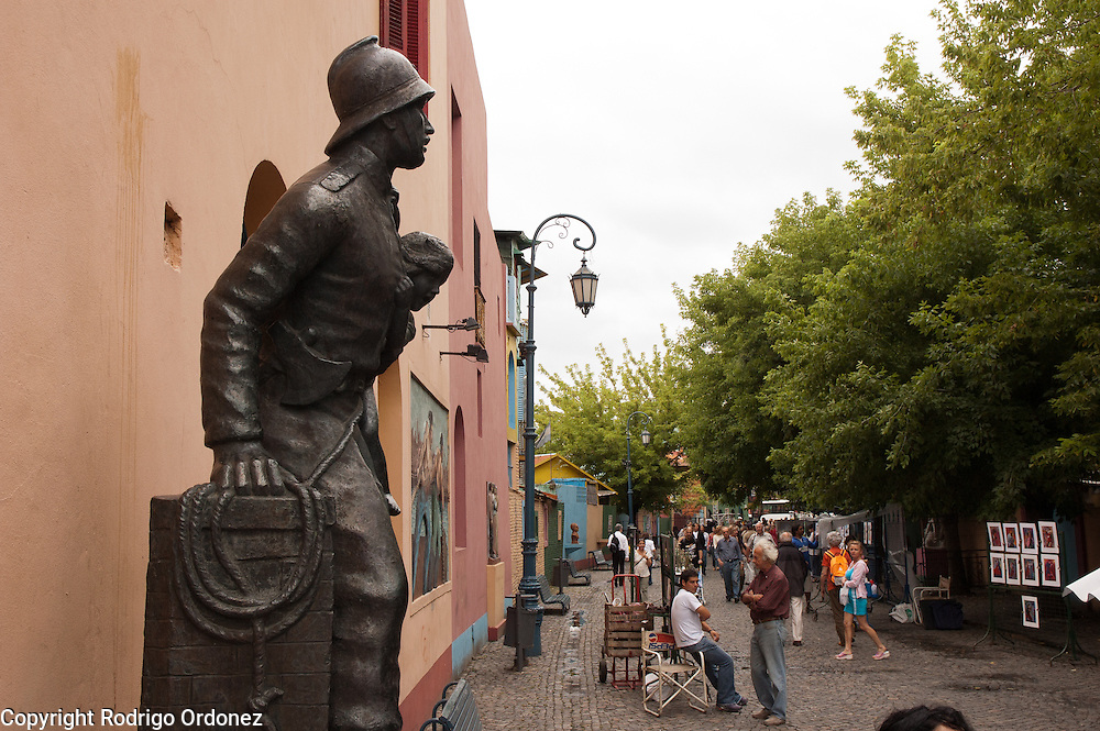 Monument to the Volunteer Firefighter, by Ernesto Scaglia, in Caminito street, in La Boca neighborhood of Buenos Aires, Argentina.<br /> Caminito is a pedestrian street created in the late 1950s by local painter Benito Quinquela Martín and other artist friends to recreate a version of the old immigrant neighborhood of La Boca, using wood and corrugated zinc painted in bright colors. Today, Caminito and the surrounding areas feature cafes, souvenir shops, tango dancers and other street performances aimed to attract tourists.