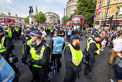 © Licensed to London News Pictures. 14/07/2018. London, UK. Police push back supporters of EDL founder Tommy Robinson ( real name Stephen Yaxley-Lennon ) and US President Donald Trump as they block a bus at Trafalgar Square during a day of demonstrations and rallies in support and opposed to US President Donald Trump and jailed EDL founder Tommy Robinson . Trump is currently in Scotland and Robinson is in HMP Hull . Photo credit: Joel Goodman/LNP