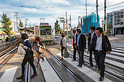 "Pedestrians walk over a crossing in front of a tram on the Toden Arakawa Line in Tokyo, Japan Friday October 12th 2012. Nick-named the ""Chin-chin"" Densha"" after the sound it bell used to make the Toden Arakawa Line is the last tram-line in Tokyo."