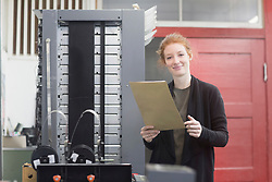 Portrait of smiling woman standing by printing press machine and holding document
