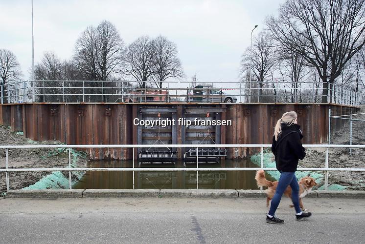 Nederland, Mook, 9-2-2020 Het water in de Maas in Noord Limburg staat hoog. Uiterwaarden lopen op sommige plekken onder en de veerpont tussen Cuyk en Middelaar is uit de vaart. Er zijn ook enkele recent voltooide hoogwater projecten in werking. Zo worden kleine beekjes en stroompjes in het gebied afgesloten om te voorkomen dat het maaswater naar het binnenland vloeit zoals hier bij Afferden waar een nieuwe afsluiter in de Eckeltse Beek geplaatst is . . Foto: Flip Franssen