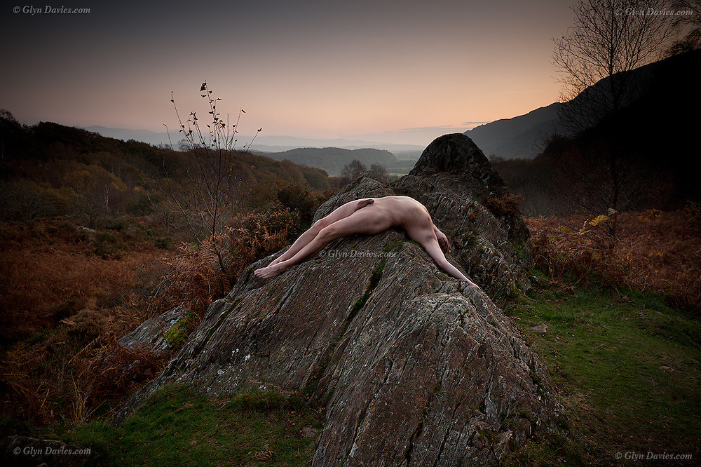 """Nominated in 10th (2017) International Colour Awards (Nude category) <br /> <br /> """"It was dusk and a gentle mist hung in the valleys, illuminated only by the last glimmer of Autumnal daylight. There was delicate moisture in the air and a slight dampness on the short grass surrounding the rock. Rich, earthy smells surrounded me, from the bracken and ancient woodland adjacent to the outcrop. Above the sound of a gurgling brook I could hear a thrush singing somewhere in the distance. Apart from that there was relative silence; no cars, no planes, no groups of chatty 'ramblers on a mission', just me in what felt like a lost valley. I was alone and had found perfect solitude. <br /> <br /> I enjoyed the feeling of the cool, almost prickly, sheep-mown grass on the soles of my feet, but the rock was warm having basked during a day of unbroken sunshine under clear blue skies.  Although the rocky outcrop looked smooth from a distance it was rough beneath my skin, making my body feel vulnerable to its sharp surface. I enjoyed the sensation nevertheless, feeling utterly and intimately connected to 'my' rock, a rock carved by glaciers millions of years ago, scratched and smoothed by the weight of ice, but today it was just me, an insignificant speck on the planet. Yet the planet means everything to me; I feel it, see it, and hear it. It provides for me, nourishes me and I am a part of it nevertheless. <br /> <br /> As the melody of the Song Thrush drifted away, I lay relaxed, supine, as much of my skin surface in contact with the rock as I could manage, facing the darkening universe above. The rock supported me, it seemed as if the Earth itself was carrying me, a fragile, perishable organic figure, exposed to the air and the elements but wonderfully connected to the land"""""""