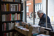 A man looks through the window of John Sandoe bookshop on 19th October 2015 in London, United Kingdom. Independent bookshop since 1957, crammed with thousands of fiction, non-fiction and classic titles