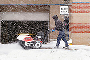 29 DECEMBER 2020 - DES MOINES, IOWA: A worker snowblows the snow off the sidewalk in downtown Des Moines during the heaviest snowfall so far of the 2020-21 winter. Des Moines was expected to get about 8 inches of snow before Wednesday morning. Statewide, across Iowa, more than 900 snowplows have been called out to clear the roads.      PHOTO BY JACK KURTZ