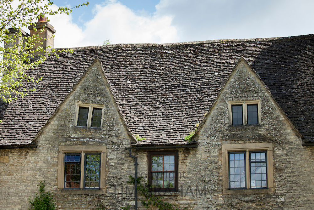 Crooked stonework of ancient cottage in the High Street in the popular country town of Burford in the Cotswolds, Oxfordshire, UK