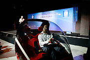 An engineer steers a concept en-v electric vehicle while Dan Akerson, chief executive officer of General Motors Co. ( GM), makes his presentation in Shanghai, China, on Wednesday, Sept. 21, 2011. China's auto market will grow by 13 million units in 10 years, Akerson said at a briefing.