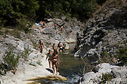 Italians enjoying the cooling waters of the Bosso River in Secchiano, Umbria, Italy. Here the crystal clear waters carve their way through the rocks as groups of people come to cool off in the Summer temperatures and hang out tanning themselves in the sun.