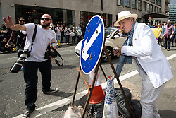 © Licensed to London News Pictures . 29/08/2015 . Manchester , UK . The actor , SIR IAN MCKELLEN , ducks behind a street sign to light a cigarette as a PR photographer tries to block other photographers from photographing the moment . Ian McKellen leads the 2015 Manchester Pride parade . Photo credit : Joel Goodman/LNP