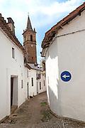 One way road sign pointing down a very narrow street, village of Alajar, Sierra de Aracena, Huelva province, Spain