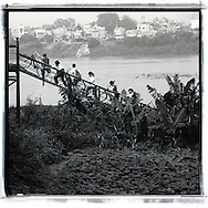 Few teenagers push their bicycle on long bien bridge. The ramp access to the island located between two arms of the red river. This island is an agricultural place.