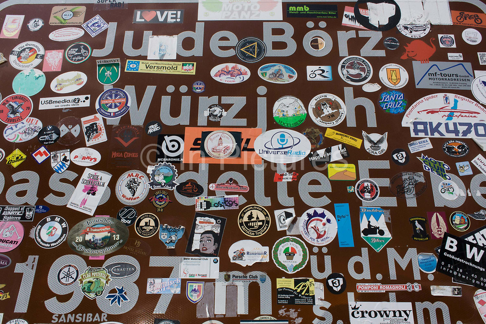 Stickers cover the signpost marking the summit of the Wurzjoch Pass, in the Puez Geisler Nature Park and on the road between Brixen-Bessanone and St Martin in Badia. Obscuring the information intended for drivers and tourists, the stickers come from all over the world: For example, many German biker clubs leave their mark plus BMW and Porsche touring groups and other motoring organisations. The Puez Geisler Nature Park is a regional park situated right in the heart of the Dolomite mountain world and is one of the most beautiful and striking in the entire Alpine region.