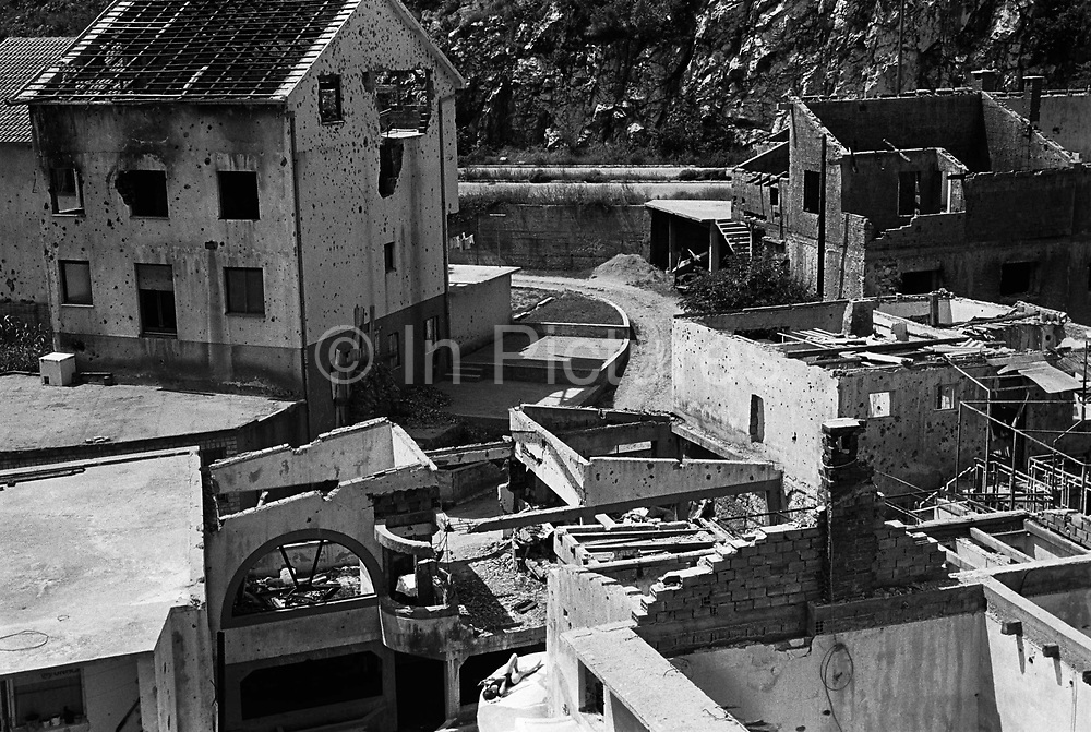 """Girl sunbathing in the ruins. It was destroyed by systemic bombardment from Croat guns during the Croat Muslim War, when the Croats endeavored to """" cleanse"""" the town of non Croats. Mostar, Bosnia and Herzegovina."""