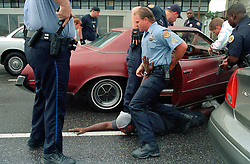 August 2003.  New Orleans, Louisiana, USA..Murder suspect James Bannister is taken down by members of the 6th district police dept in New Orleans. Bannister was later convicted of the second degree murder of Lamont Mitchell who he shot to death the previous day in the back of the same brown Buick Regal he was arrested and dragged from. Mitchell was shot and killed for little more than poking fun at men he considered friends. .Photo credit; Charlie Varley.