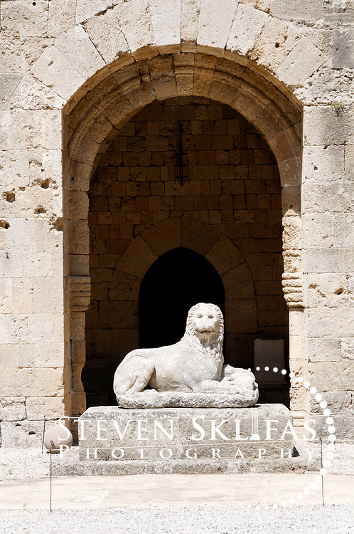 Rhodes. Greece. Ancient marble lion in the internal courtyard of the old town gothic Knights hospital. Completed in 1484, the hospital was used in times of war to nurse the sick and injured from all over Christian Europe. The old town is a UNESCO world heritage listed site and the best preserved, oldest and largest living medieval city in Europe. The 4km defensive walls were built by the Knights of St John during the 13th to 15th century to defend Western Europe against the expanding Ottoman Empire. Within the walls are a medieval warren of small alleyways and magnificent historical buildings. The island of Rhodes is the largest of the Dodecanese Island group and one of the most popular Greek Islands.