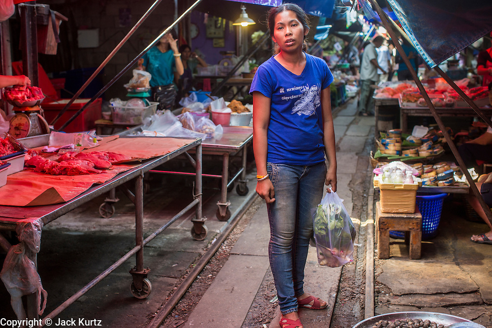 17 JANUARY 2013 - SAMUT SONGKHRAM, SAMUT SONGKHRAM, THAILAND: A woman walks through the market in Samut Songkhram. Four trains each day make the round trip from Baan Laem, near Samut Sakhon, to Samut Songkhram, the train chugs through market eight times a day (coming and going). Each time market vendors pick up their merchandise and clear the track for the train, only to set up again when the train passes. The market on the train tracks has become a tourist attraction in this part of Thailand and many tourists stop to see the train on their way to or from the floating market in Damnoen Saduak.    PHOTO BY JACK KURTZ