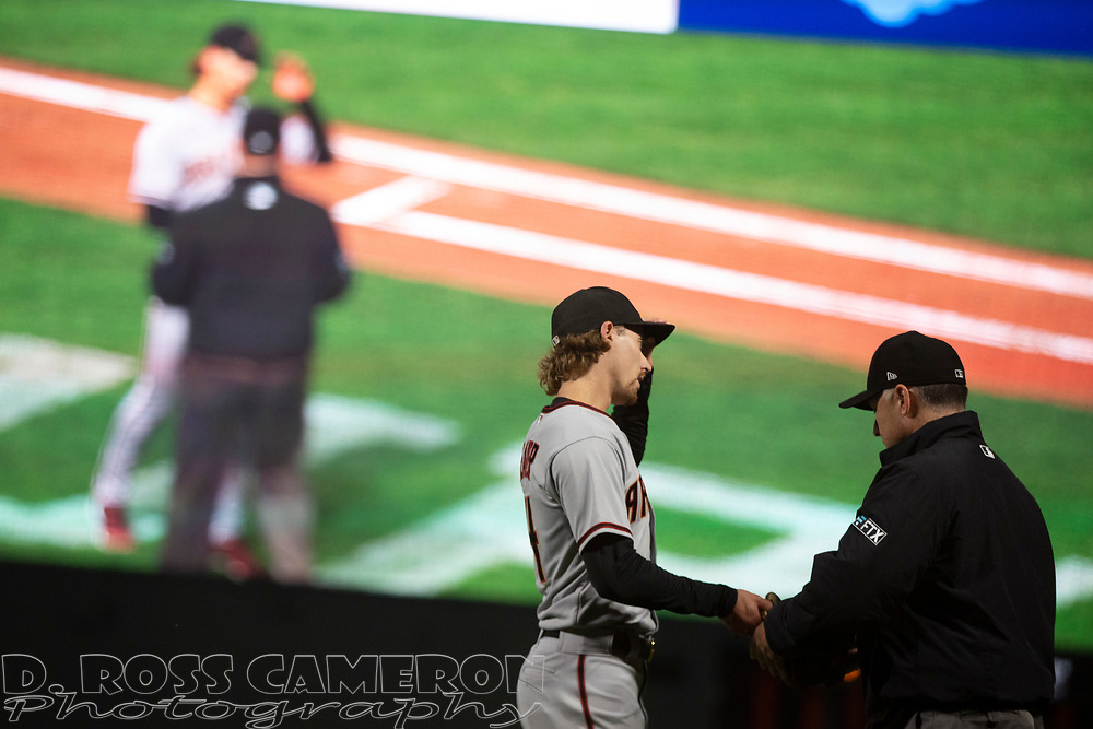 Arizona Diamondbacks starting pitcher Luke Weaver (24) has his equipment checked for foreign substances by first base umpire Dan Iassogna during the fourth inning of a baseball game, Tuesday, Sept. 28, 2021, in San Francisco. (AP Photo/D. Ross Cameron)