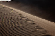 A wind storm blows sand over the ridges of the dunes, Great Sand Dunes National Park and Preserve, Colorado.