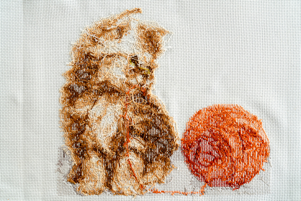 backside of embroidery with little cat and yarn ball