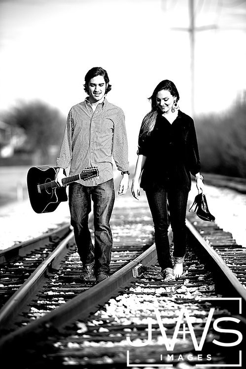 Seniors in high school walking on railroad tracks in Texas while holding the guitar.