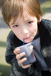 Child drinking from juice carton,