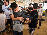 """14 JANUARY 2017 - BANGKOK, THAILAND: A child aims an empty Royal Thai Army  TAR-21 assault rifle during Children's Day activities at the King's Guard, 2nd Cavalry Division base in Bangkok. Thailand National Children's Day is celebrated on the second Saturday in January. Known as """"Wan Dek"""" in Thailand, Children's Day is celebrated to give children the opportunity to have fun and to create awareness about their significant role towards the development of the country. Many government offices open to tours and military bases hold special children's day events. It was established as a holiday in 1955.       PHOTO BY JACK KURTZ"""