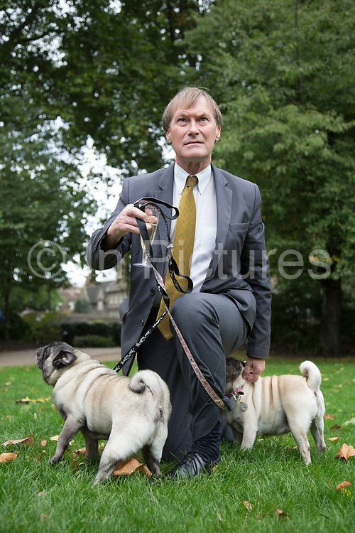 London, UK. Thursday 10th October 2013. David Amess MP with his two Pugs Lilly and Bo. MPs and their dogs competing in the Westminster Dog of the Year competition celebrates the unique bond between man and dog - and aims to promote responsible dog ownership.
