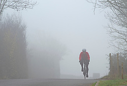 © Licensed to London News Pictures 03/03/2021. <br /> Swanley, UK. A cyclist in a country lane near Swanley in Kent. The Met Office has issued a misty fog warning for most of the day in the South East. Photo credit:Grant Falvey/LNP