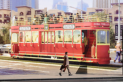 Man walks past large billboard advertising the new Dubai Trolley - a hydrogen fuel cell powered tourist tram in Dubai United Arab Emirates