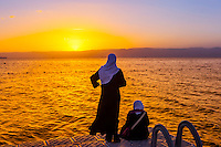 Jordanian women watching the sunset across the Gulf of Aqaba, Red Sea, Jordan from a dock at the Radisson Blu Tala Bay Resort.