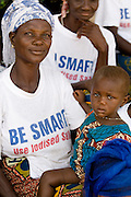 A woman who wears a t-shirt promoting iodized salt holds a child on her lap.