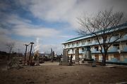 Ishinomaki  Minami Hamacho  recueil -  11 Mars 2012.Face à la mer, un bâtiment en beton a résisté. Juste là se trouvait un sanctuaire shintoïste qui fut emporté et détruit par la vague. A quelques mettre sur la gauche sélève une montagne de débris. Derrière moi, samoncèlent des centaines de carcasses de voitures