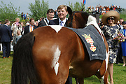 Koning Willem Alexander en Koningin Maxima op provinciebezoek in Utrecht.<br /> <br /> King Willem Alexander and Queen Maxima visit the province of  Utrecht<br /> <br /> Op de foto: Koning Willem-Alexander schikt het tuig van een paard tijdens zijn bezoek aan IJsselstein en Koningin Maxima praat met de ouderen<br /> <br /> King Willem-Alexander suitable harness a horse during his visit to Queen Maxima IJsselstein and talk to the elderly