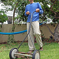 A man mows the grass with an environmentally-friendly push reel mower.