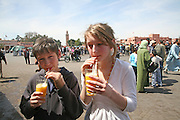 Children drinking fresh ornage juice in Place Gema el-Fna, Marrakech, Morocco