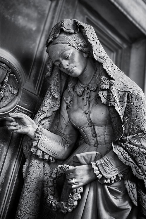 Heavens Gate - Black and white art photo of the stone sculpture of a  mourning widow who is bringing a crown and knocking on a sepulcher's bronze door, which holds the bas relief of an hourglass, a classic symbol of the passing of time. This theme of the sorrowful survivor in front of the sepulcher's door comes from the Monument dedicated to Maria Christina, Duchess of Teschen, Maria Theresa of Austria's daughter, a neoclassical sculpture. In this version the widow is wearing fashionable clothes, which have been accurately represented, and her openwork shawl. Sculptor G. B. Cevasco 1875. Section A, no 38, The monumental tombs of the Staglieno Monumental Cemetery, Genoa, Italy .<br /> <br /> Visit our PEOPLE & PLACES PHOTO ART COLLECTIONS for more photos to buy as buy as wall art prints https://www.photoshelter.com/mem/images/index#/C00001WetsxVxNTo/ .<br /> <br /> Visit our LANDSCAPE PHOTO ART PRINT COLLECTIONS for more wall art photos to browse https://funkystock.photoshelter.com/gallery-collection/Places-Landscape-Photo-art-Prints-by-Photographer-Paul-Williams/C00001WetsxVxNTo