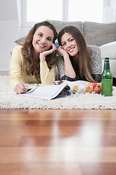 Two smiling female friends lying side by side on carpet at home