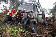 Bus van support vehicle stuck slipping and trying to get past fallen trees, with people trying to help. Bikers on 'the World's most dangerous road' down to Coroico in the Yungas, La Paz province, Bolivia.