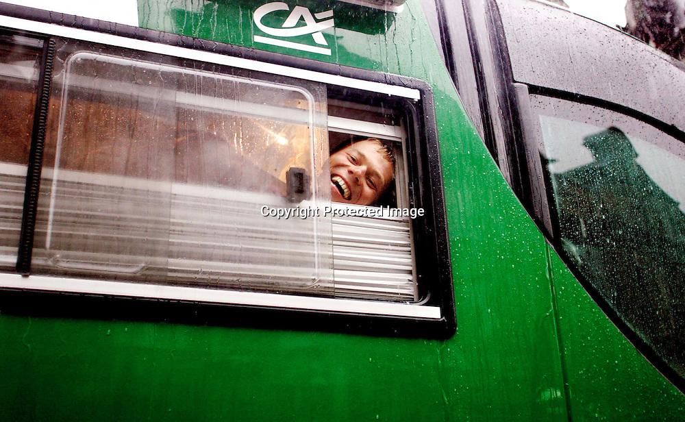 Arras/Frankrike, 20040707.Tour de France. Thor Hushovd titter ut av lagbussen, mens hele det norske pressekorpset blir overfalt av regnet...Foto: Daniel Sannum Lauten/Dagbladet